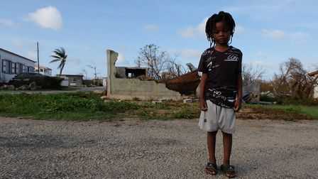 TJ Hickson, 5, stands outdoors near partially destroyed buildings on the island of Anguilla, which w