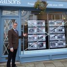 Anthony Burn outside Watsons of Holt, which is advertising houses for sale at 1940s prices. Picture: