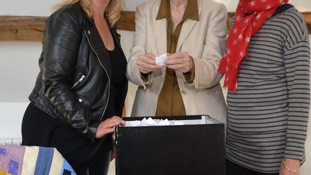 County Councillor Dr Marie Strong (center) selecting the winning ticket and joined by Mary Blue Brad