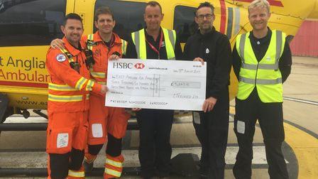 An air ambulance crew is presented with a cheque totalling over £3,6000, which was generated from th