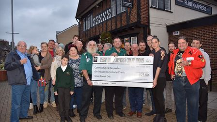 Landlords Charlton and Jo Day with money raiser John Tango Mail, hand over a cheque to Community F