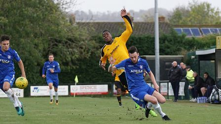 Lowestoft's Rory McAuley comes under pressure from Merstham's RJ Pingling. Picture: Shirley D Whitlo