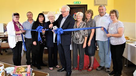 Norman Lamb MP cuts the ribbon to officially open the club surrounded by volunteers, with Ros Peeble