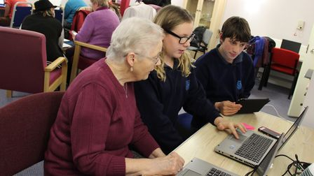 Teenagers helping teach technology skills to older Norfolk residents at a previous Digital Buddies p