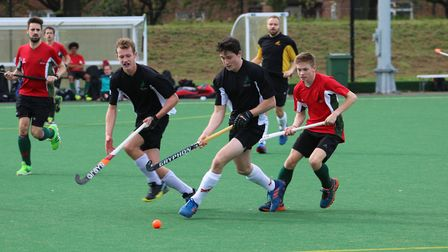 Max Laming and Tom Harris in black chase the ball whilst being closed down by Jonathan Chaney Baxter