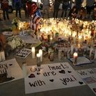 A girl places candles at a memorial for victims of the mass shooting in Las Vegas. (AP Photo/Marcio