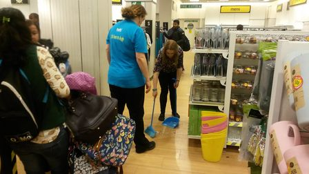 A staff member sweeping up broken glass at Tofs clearance sale. Photo: Jacob Massey