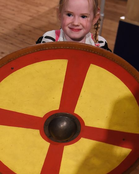Myrtle Donhou, six, holds a heavy replica shield at the Saturday Knight Fever event at Norwich Castl