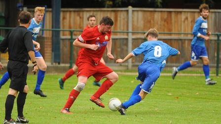 Wroxham Reserves' Josh Pond (blue) and Caister's George Barnden fight for possession. Picture: DENIS