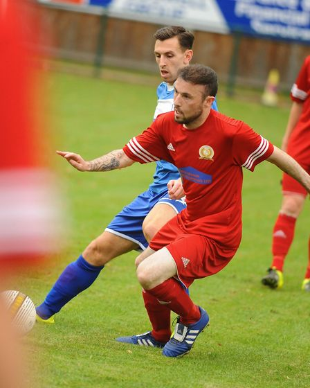 Caister's Gaz Ward (red) is tracked by Wroxham Reserves' Jordan Bond. Picture: DENISE BRADLEY