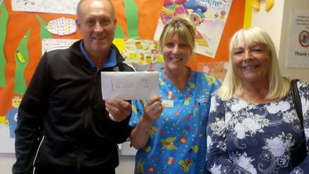 Pictured is Gary High (left) and Elaine High (right) presenting the money to Jane Whiteside - HG The