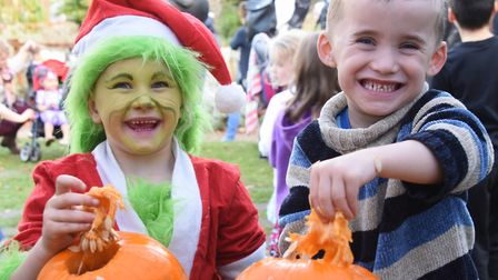 The Grinch, Ella-Shai Norman, six, and Reggie Dent, five, scoop out their pumpkins at the Pumpkin Fe