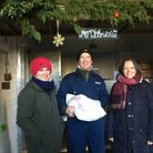 Nicila Collier, right, a volunteer with the Anon Street Team, is given a turkey by farmers James Gra