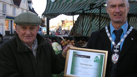 Tony Keeling is presented with a commemorative certificate by Robert Savage, mayor of Wymondham. Pic