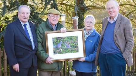 Wildlife photographer Chris Knights (second left) presents his photograph to Janet Baldwin, in the g
