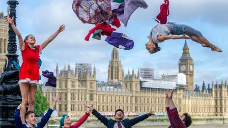Acrobats from the group Lost in Translation perform a stunt in front of the Houses of Parliament in
