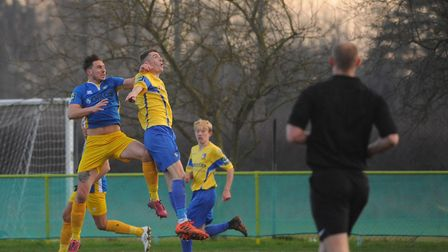 Liam Jackson (yellow) in an aerial battle for Norwich United against Canvey Island. Picture: DENISE