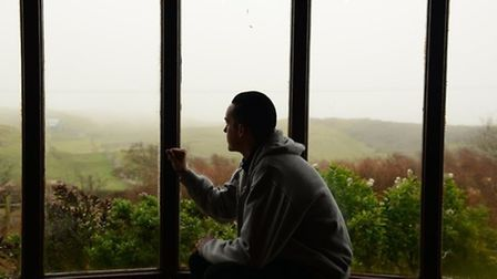Mental health. Pictured: A young man experiencing depression sits by a window. Picture: Newscast Onl
