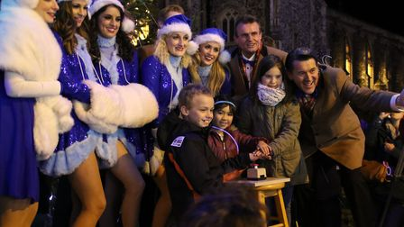 Poster competition winners join the Cromer Pier Christmas Show cast at the switch-on of the town's C