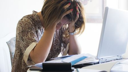 An image of a woman who has become stressed because of the bills. Photo: Newnow/Getty Images/iStock