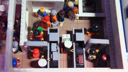Passengers queuing through the metal detector arches at the lego airport display, at the Brick Wonde