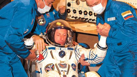 Russian experts help astronaut Michael Foale to stand up after inspecting his space suit just befor