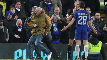 A home fan is escorted away after getting on the pitch during the Third Round FA Cup Replay match at