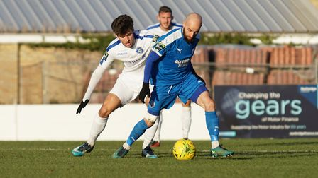 Lowestoft's Matthew Foy tracks Leiston's former Town player Chris Henderson during the Boxing Day ga