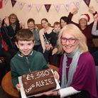 Alfie Oswick, nine, of Cawston, hands over a chocolate cake to Janet Money of Dereham Cancer Care, r