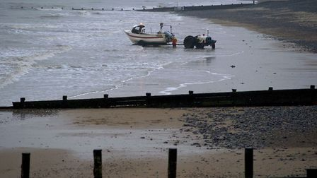 Fishermen bringing the boat onto the beach at Cromer. Photo by Mark Bullimore