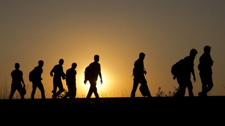 A group of refugees walk on the railway tracks after crossing from Serbia, in Roszke, Hungary, Tuesd