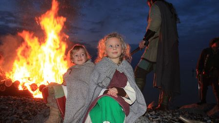 Young re-enactment group members Alicia and Ruby watch the boat-burning on the beach. Photo: KAREN B