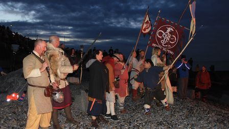 Re-enactors watch the ceremonial boat-burning on the beach. Photo: KAREN BETHELL