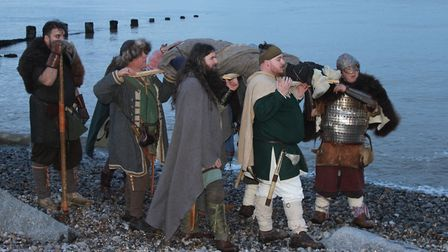 Re-enactors carrying the 'body' of a Viking leader to the longboat funeral pyre. Photo: KAREN BETHEL