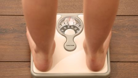 Posed photo of a person using a set of weighing scales. Photo: Chris Radburn/PA Wire