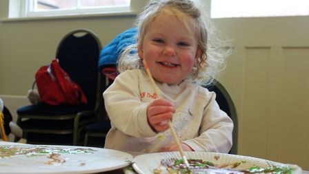 Two-year-old Sophie Wallace mixing colours for her Viking shield at one of the children's workshops