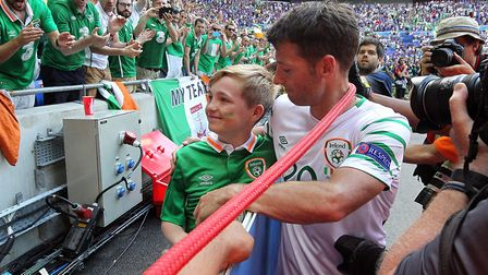 Wes Hoolahan gives his boots to a young fan at the end of the Euro 2016 match against France at Stad