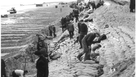 Filling sandbags at Sea Palling and the lines on beach caused by the activity of the bulldozers repa
