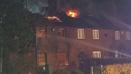 Fire crews are tackling a blaze which has spread across three terraced houses in west Norfolk. Photo