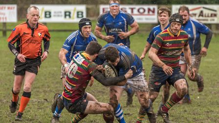 Diss plough forward through the mud during Saturday's cup semi-final against Norwich. Picture: Andy