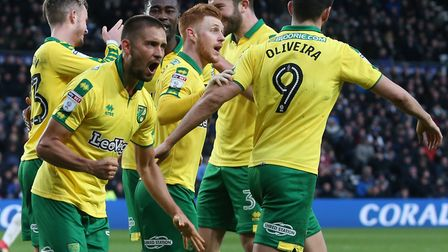 Moritz Leitner gets excited as James Maddison is mobbed by the rest of his Norwich City team-mates f
