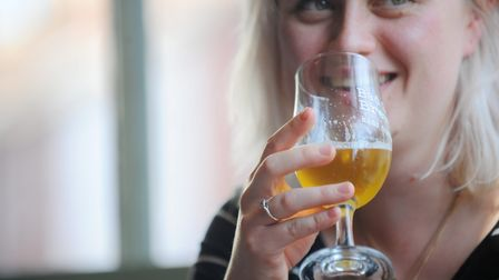 A woman drinking beer at the Plasterers Arms, Cowgate, Norwich. Photo : Steve Adams
