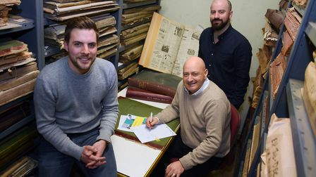 Archant chief executive, Jeff Henry, front right, signs the contract in Archant's archive with Joe D