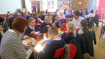 Children eating lunch with children's author Steve Skidmore, as he opened the new library at All Sai