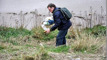 Jan Eric Visser collecting rubbish from beside the Great Ouse for making into art as part of the Tra