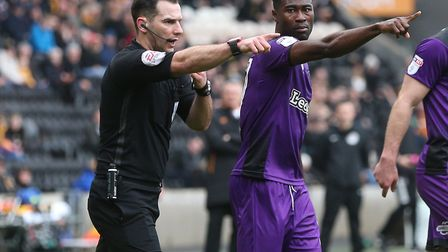 Alex Tettey helps referee Tim Robinson point to the spot during Norwich City's 4-3 defeat at Hull -