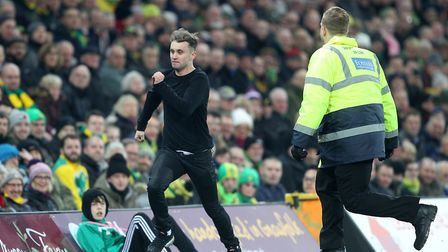 A Notts Forest fan invades the pitch and is ejected by stewards during the Sky Bet Championship matc
