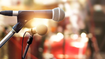 Microphone on concert stage background. Photo: ipopba/GettyImages/istockphoto