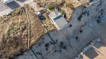 Bungalows in Hemsby hang precariously close to the edge of the sandy cliff along the beach Photo: Bl