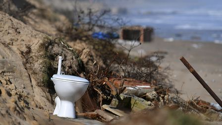 A toilet sits on the beach after falling from a partially-collapsed house on the cliff edge at The M